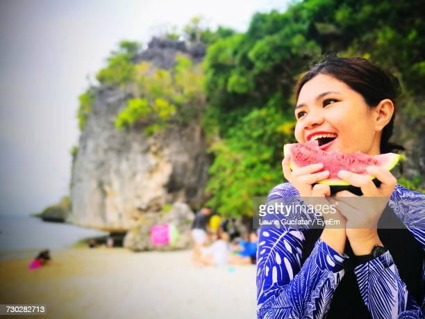 Young Woman Eating Watermelon At Beach