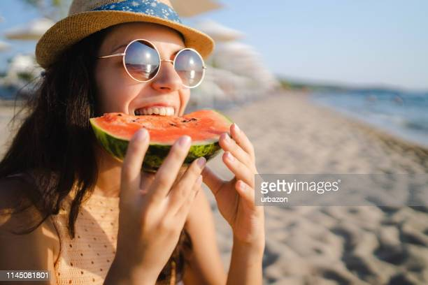 young woman eating watermelon on the beach - watermelon stock pictures, royalty-free photos & images