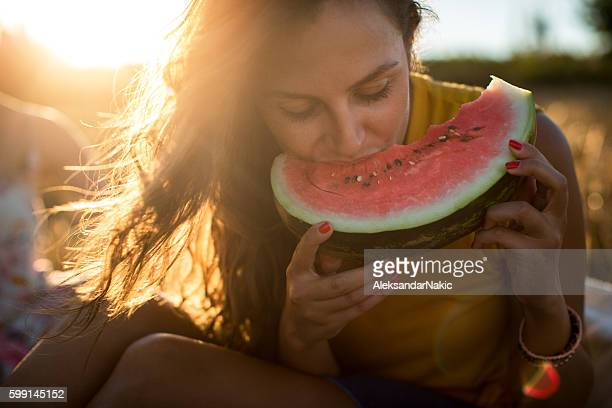 young woman eating watermelon outdoors - watermelon stock pictures, royalty-free photos & images