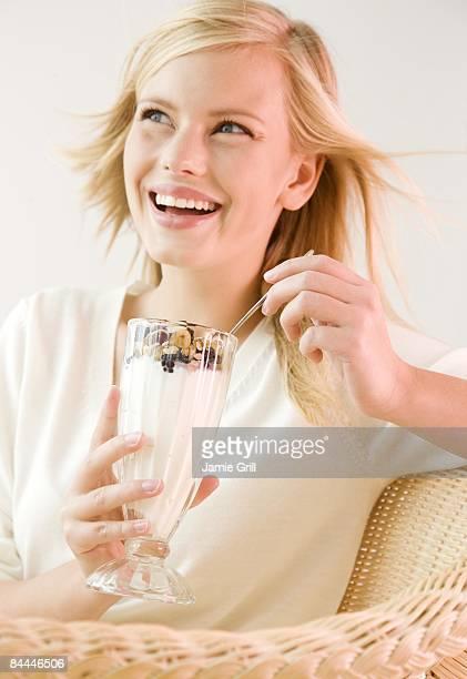 Young woman eating yogurt and granola