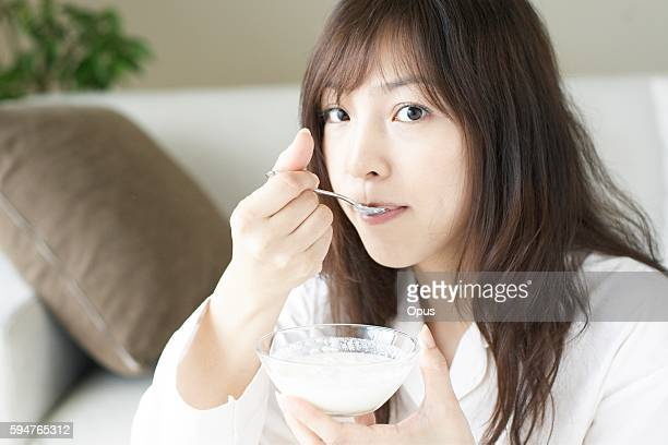Young woman eating yogurt for breakfast
