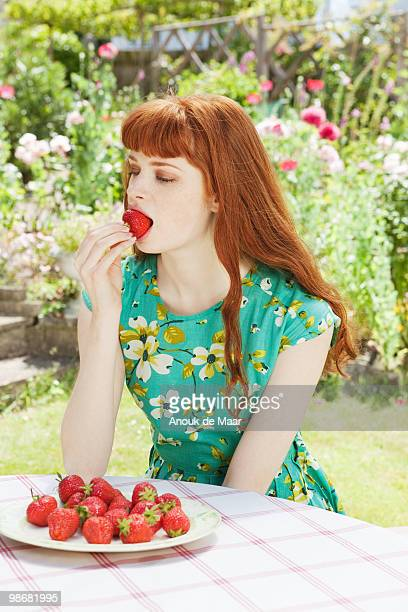 young woman eats strawberries in garden.