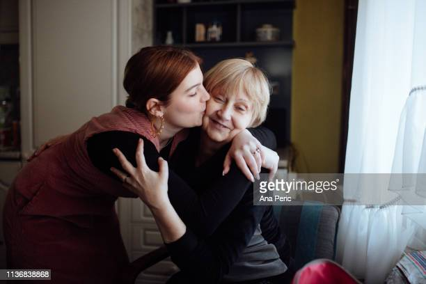 young woman embracing and kissing her mother - só adultos imagens e fotografias de stock