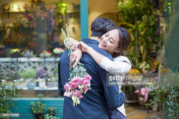 Young woman embracing boyfriend with flowers