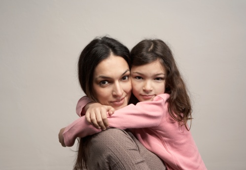 Young woman embracing daughter (6-8), portrait - gettyimageskorea