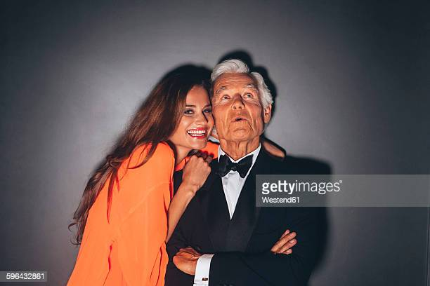 young woman embracing elegant senior man - sugar daddy stock photos and pictures