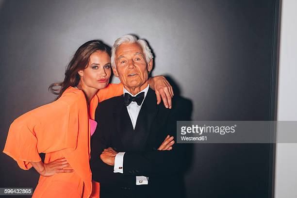 young woman embracing elegant senior man - may december romance stock photos and pictures