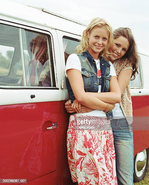 Young woman embracing friend by camper van, smiling, portrait