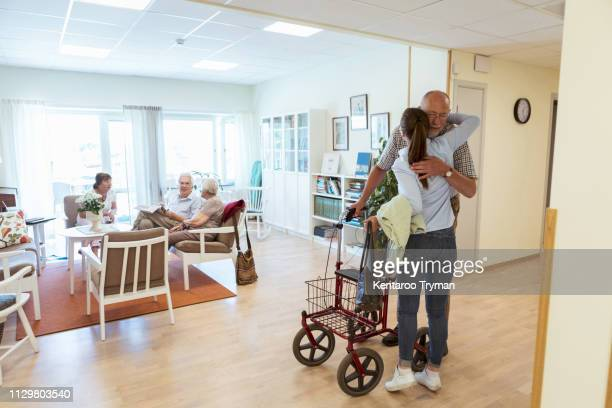 young woman embracing grandfather during visit at nursing home - retirement community stock pictures, royalty-free photos & images