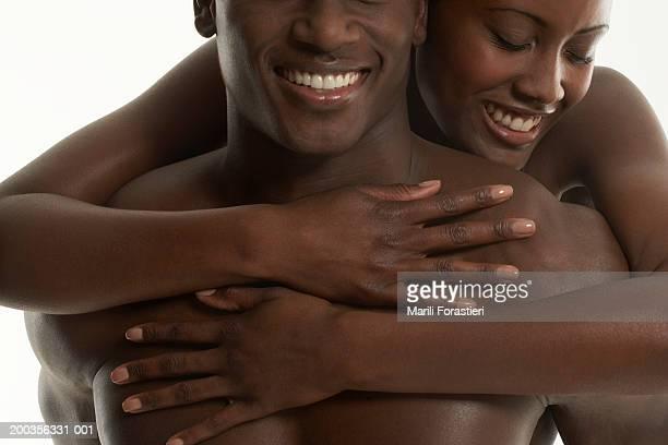 Young woman embracing man, smiling, close-up