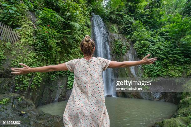 Young woman embracing nature at the waterfalls in Bali