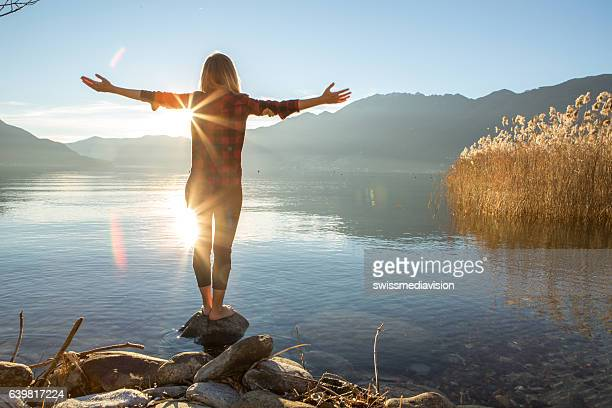 young woman embracing nature, mountain lake - sonnenlicht stock-fotos und bilder