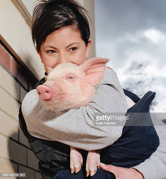 Young woman embracing piglet, outdoors