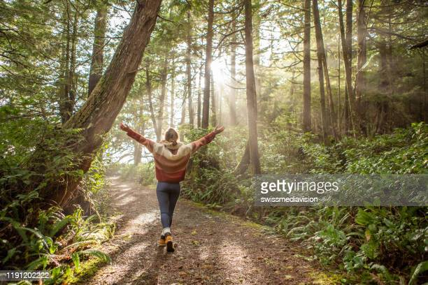 young woman embracing rainforest standing in sunbeams illuminating the trees - vancouver island stock pictures, royalty-free photos & images