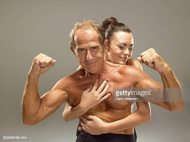 young woman embracing senior man, smiling - pareja hombre mayor y mujer joven fotografías e imágenes de stock