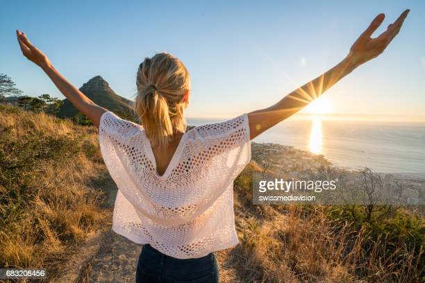 Young woman embracing sunset in nature