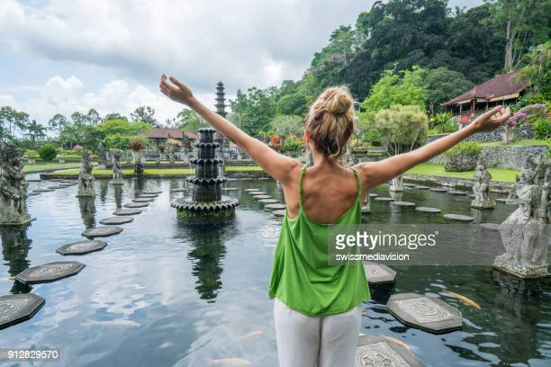 young woman embracing tirta gangga temple, bali, indonesia - eco tourism stock pictures, royalty-free photos & images