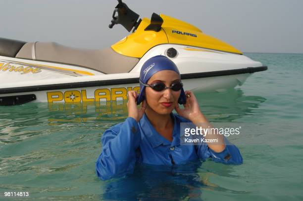 A young woman emerges from the sea after a jetski in Kish a resort island in the Persian Gulf Iran 3rd July 2003 She is wearing a swimming cap and a...