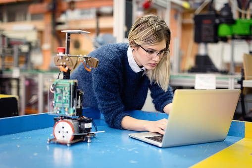 Young woman engineer working on robotics project 883132748