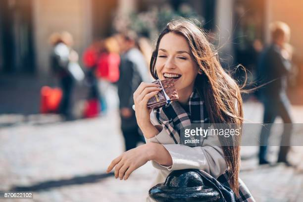 young woman enjoying a chocolate bar outdoors - barra de chocolate imagens e fotografias de stock