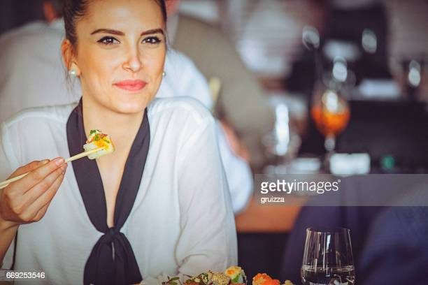 young woman enjoying a lunch time at asian restaurant - sushi restaurant stock photos and pictures