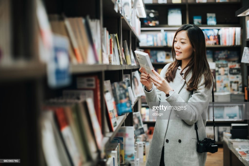 Young woman enjoying a quiet time reading book in book store : Stock Photo