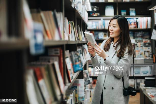 young woman enjoying a quiet time reading book in book store - book shop stock pictures, royalty-free photos & images