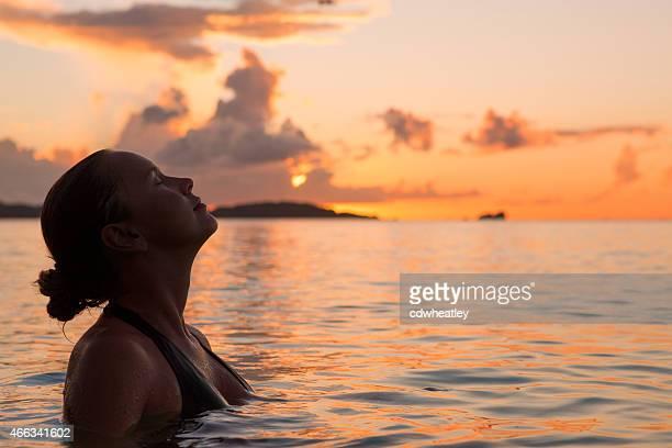 mujer joven disfruta de una zambullida en las aguas del caribe durante la puesta de sol - lugar turístico fotografías e imágenes de stock
