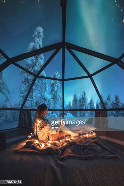 young woman enjoying a view of the northern lights - finland stock pictures, royalty-free photos & images