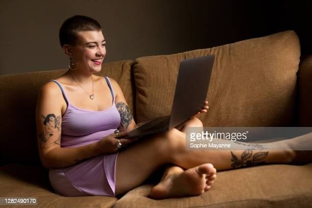 a young woman enjoying an online date - sleeveless dress stock pictures, royalty-free photos & images