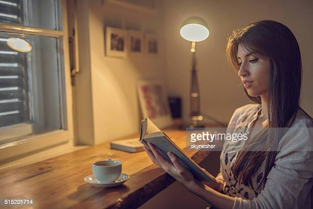 Young woman enjoying at home and reading a book.
