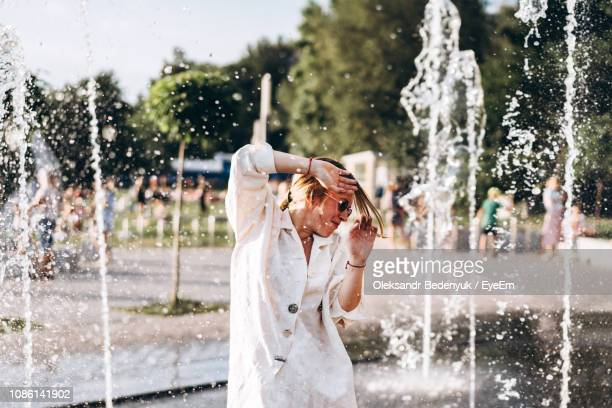 young woman enjoying at water fountain - 噴水 ストックフォトと画像