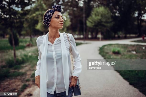 mulher nova que aprecia o dia do outono no parque da cidade - fita de cabelo - fotografias e filmes do acervo
