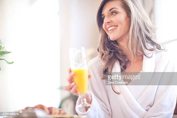 Young woman enjoying breakfast in bed