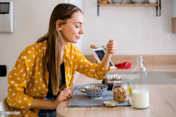 young woman enjoying breakfast in kitchen at home - gezonde voeding stockfoto's en -beelden