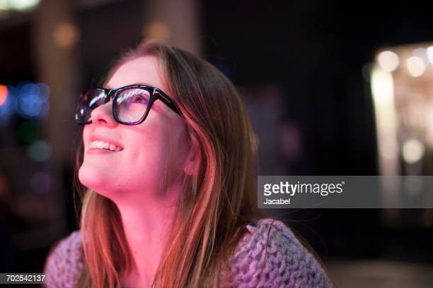 young woman enjoying bright neon lights of street, london, uk - illuminate stock photos and pictures