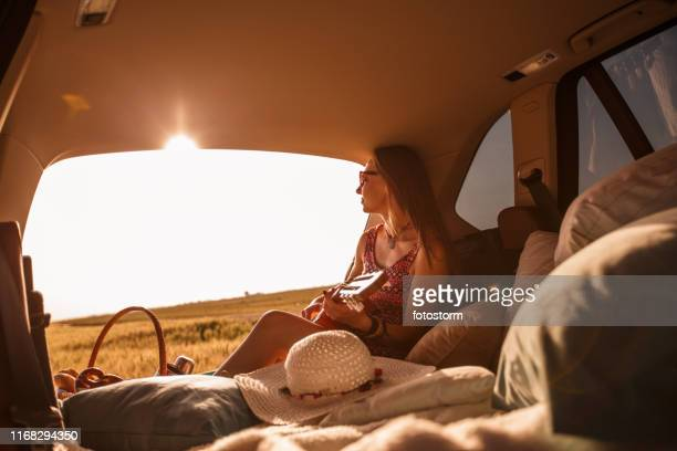 Young woman enjoying camping while watching beautiful sunset and playing guitar