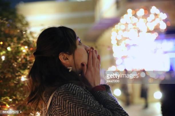 クリスマス イルミネーションを楽しんでいる若い女性