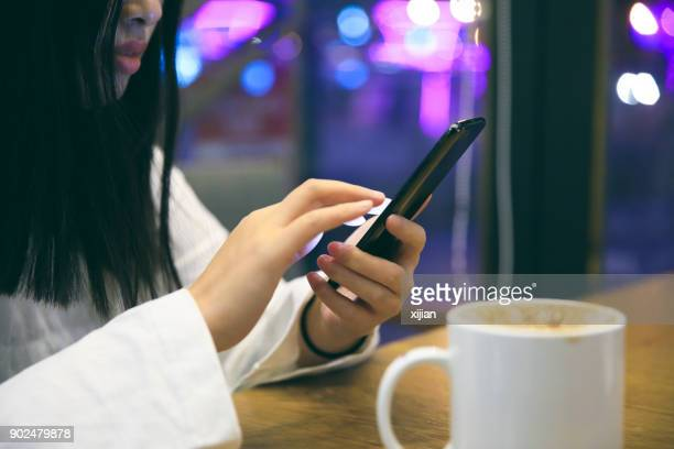 Young woman enjoying coffee and using a smart phone