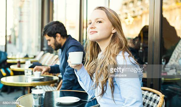 young woman enjoying coffee in a sidewalk cafeteria - stranger stock photos and pictures