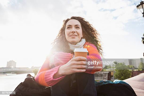 Young woman enjoying coffee to go in the morning