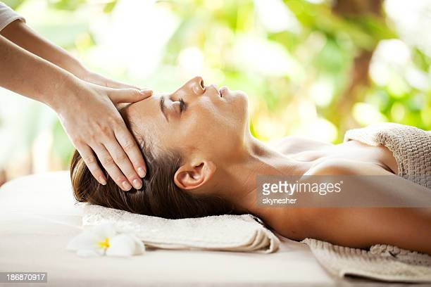 Young woman enjoying during head massage at tropical spa resort.