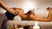 Young woman enjoying face massage in spa salon