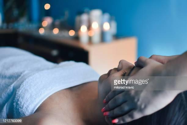 jovem curtindo massagem facial em salão de spa - instruções - fotografias e filmes do acervo