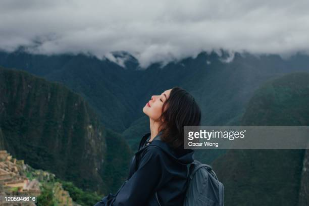 young woman enjoying fresh air on the mountain of machu picchu in peru - beauty in nature stock pictures, royalty-free photos & images