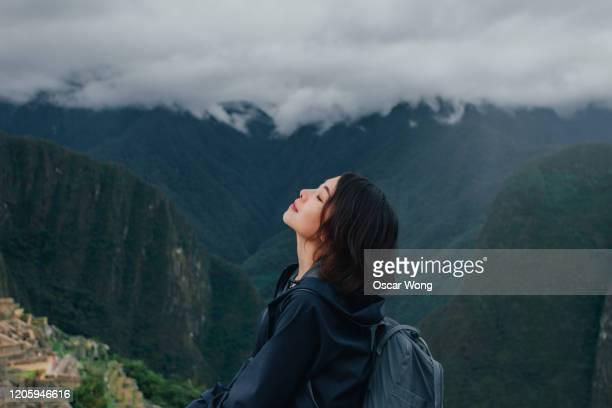 young woman enjoying fresh air on the mountain of machu picchu in peru - paisajes de peru fotografías e imágenes de stock