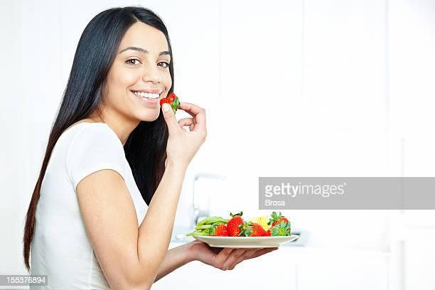 Jeune femme profitant d'une salade de fruits
