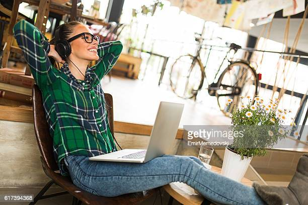 Young woman enjoying good music while resting in cafe.