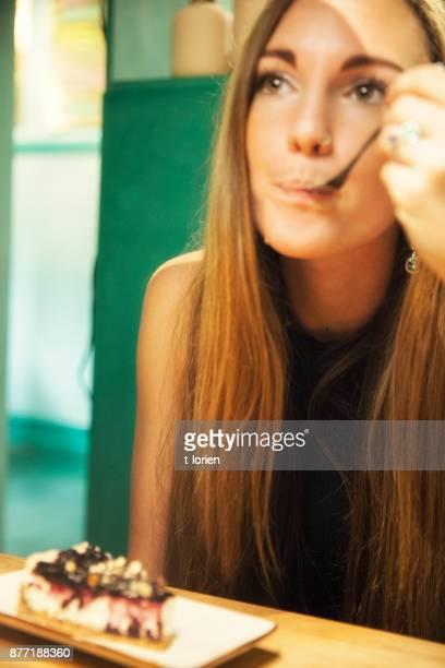 Young woman enjoying her cheesecake.