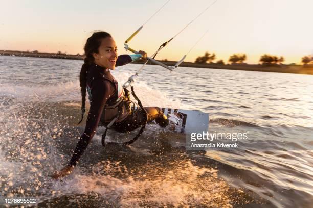 young woman enjoying her kitesurfing success. - seguir atividade móvel imagens e fotografias de stock